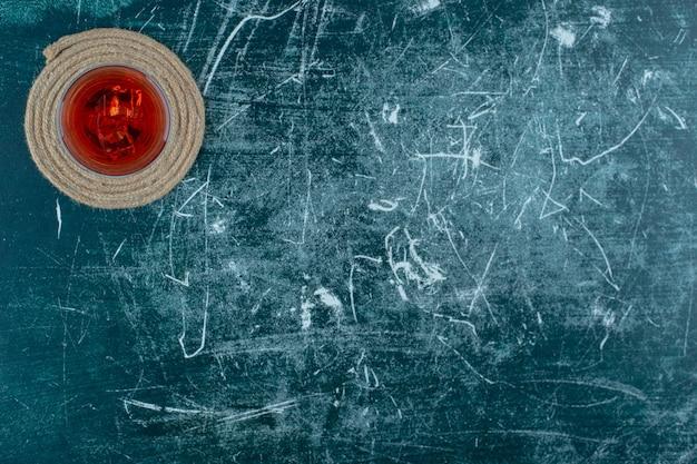 Succo di ciliegia in un bicchiere sul sottopentola, sullo sfondo di marmo.