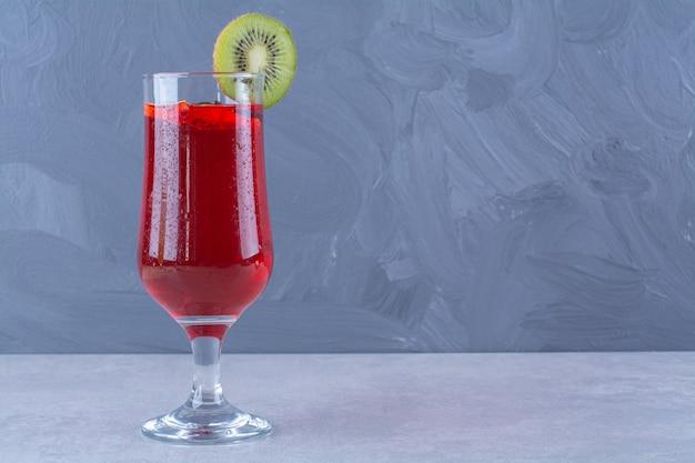 Succo di ciliegia in un bicchiere con fetta di kiwi sul tavolo di marmo.