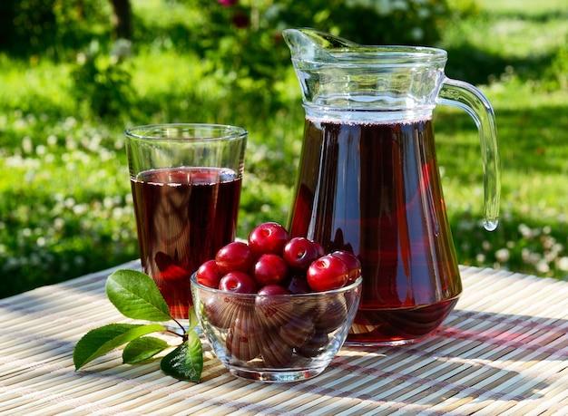 Вишневый сок в стакане и графине с вишней на естественном фоне