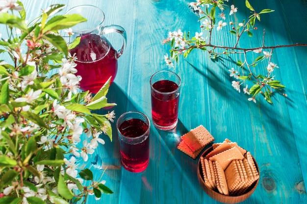 クッキーの横にあるガラスのテーブルのチェリージュース