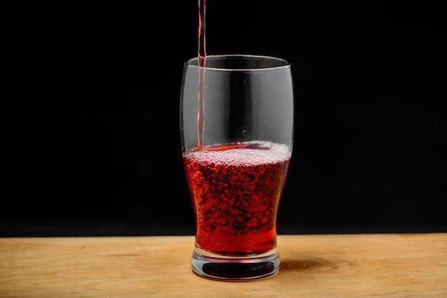 Вишневый сок, наливая в стакан на деревянный стол
