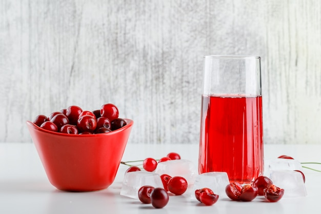 Cherry juice with cherries, ice cubes in a glass on white