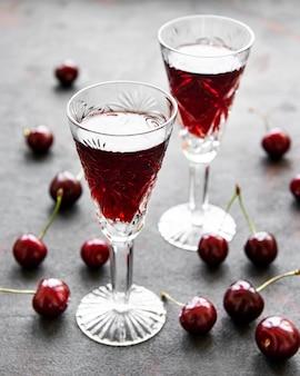 Вишневый ликер в стакане и свежие фрукты на черной бетонной поверхности