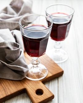 Вишневый ликер в стакане и свежие фрукты на деревянном столе