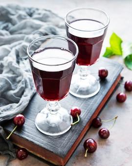 Вишневый ликер в стакане и свежие фрукты