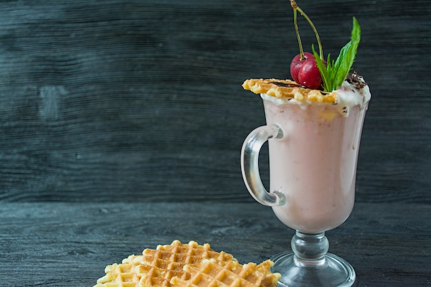 Cherry milkshake with ice cream and whipped cream, marshmallows, cookies, waffles, served in a glass cup.