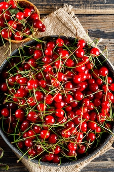 Cherry in pan and basket on wooden and piece of sack.