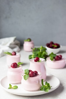 Cherry panna cotta with fresh cherries and mint in jars