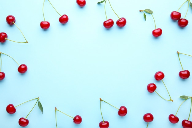 Cherry pattern. flat lay of cherries on blue with copy space.