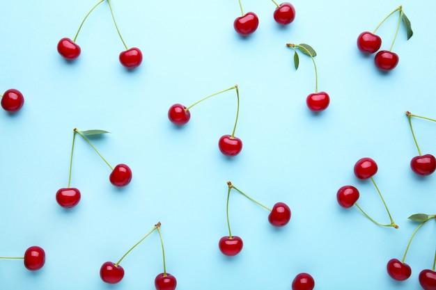 Cherry pattern. flat lay of cherries on blue.