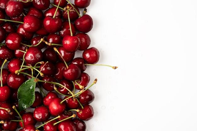 흰색 배경에 체리 빨간색 신선한 체리와 테이블에 체리 흩어져있는 체리