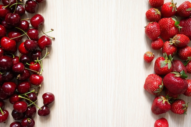Cherry and strawberry on a white wood