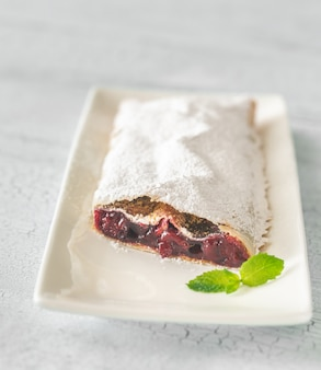 Cherry strudel on the white plate