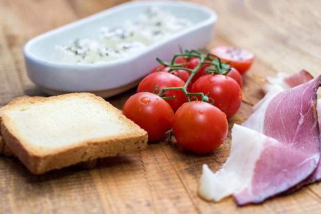 Помидоры черри, сыр и прошутто с тостом на деревянном столе