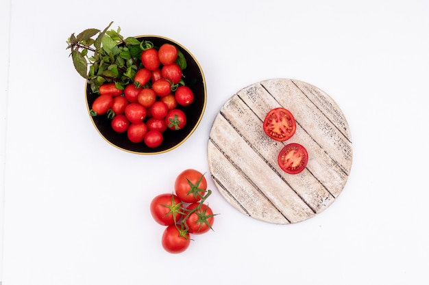 Cherry tomato and greens in black bowl tomatoes on wooden board isolated on white surface
