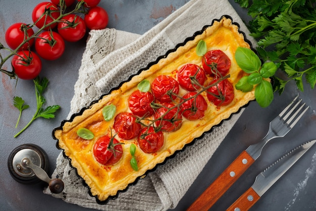 Помидоры черри и сырный пирог на темной поверхности