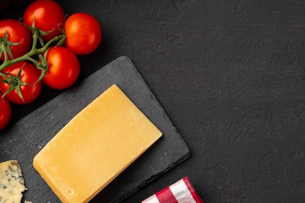 Помидоры черри и кусок сыра на черном столе
