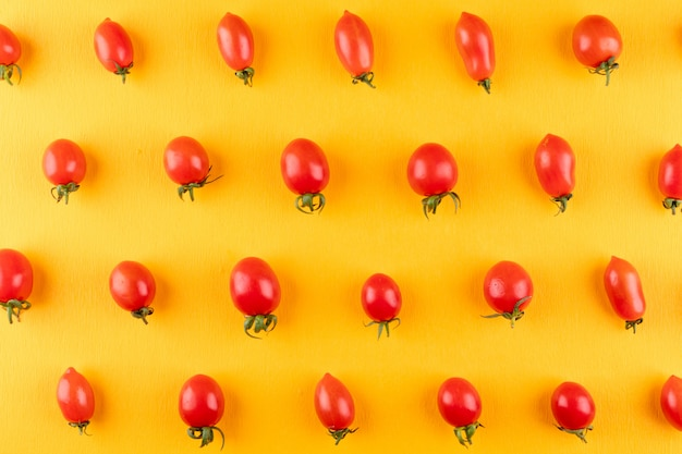 Cherry tomatoes arranged row by row on yellow
