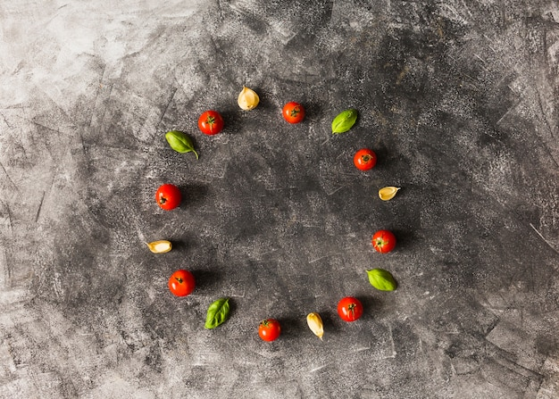 Cherry tomatoes; basil and garlic cloves arranged in circular frame on grunge background