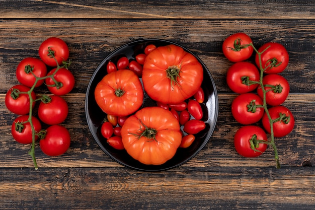 Cherry tomatoes and big tomatoes in buddha bowl on a wooden table