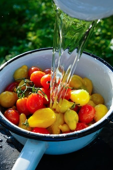 Cherry tomatoes bowl cleaning with a stream of water