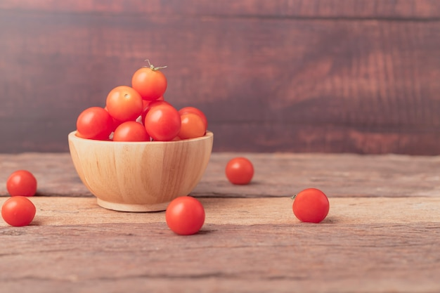 Cherry tomatoes in a bowl place on the wooden table
