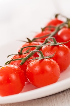 Cherry tomatoes on a branch in a plate