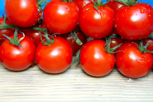 Cherry tomatoes on branches that lie on kitchen board sprinkle or pour water.
