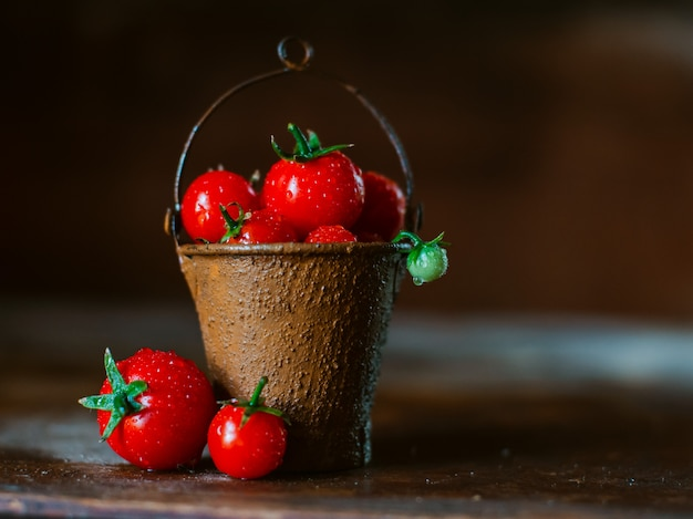 Cherry tomatoes in a decorative rusty old bucket on a dark rustic background.
