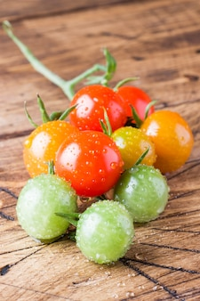 Cherry tomatoes in drops on a wooden table. a branch of multi-colored tomato green, yellow and red.