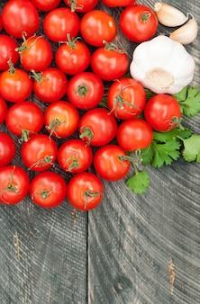 チェリートマト、ニンニク、ハーブの木製の背景。野菜の背景。上面図