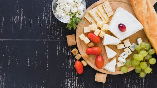 Cherry tomatoes, grapes, cheese blocks and baguette on round chopping board over the textured backdrop