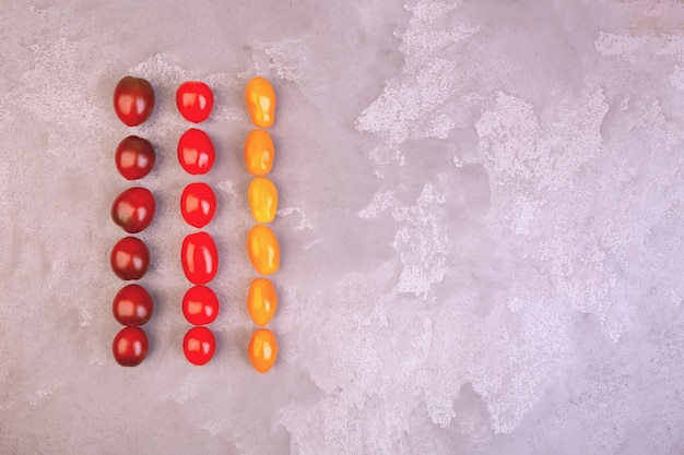 Cherry tomatoes on gray marble background. copyspace.