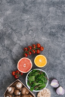 Cherry tomatoes; halved citrus fruit; spinach; mushrooms; onion and rice puffed cake on concrete backdrop