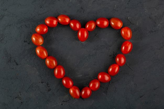 チェリートマトのハート型の暗い机の上の赤いチェリートマト