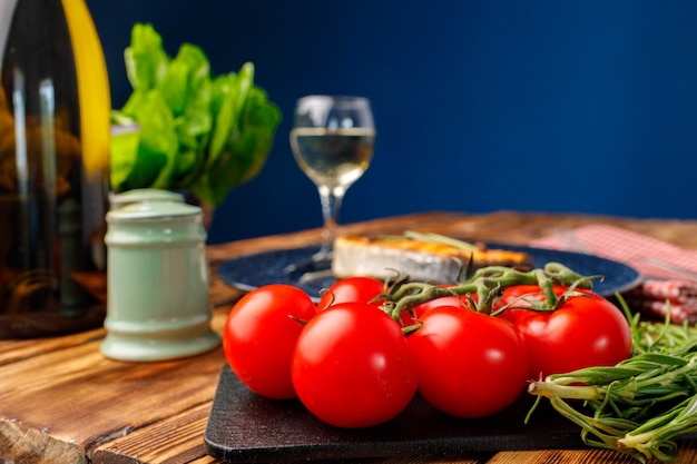 Cherry tomatoes and herbs on wooden table with bottle of wine close up