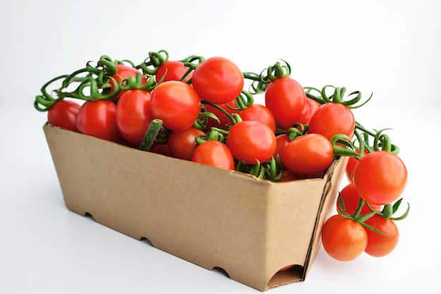 Помидоры черри в бумажной таре. свежие помидоры черри в коробке на белом фоне.