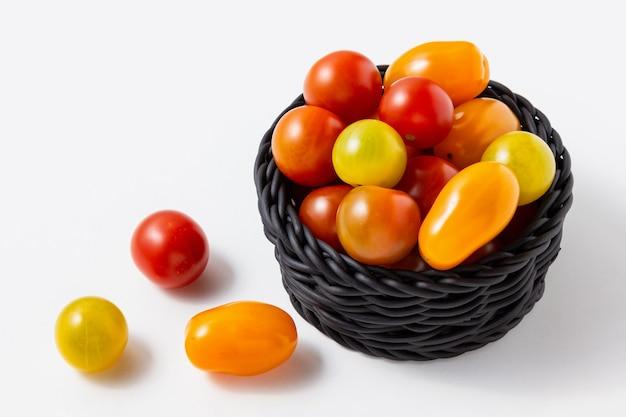 흰색 바탕에 바구니에 체리 토마토입니다. 신선한 야채의 측면 보기입니다.