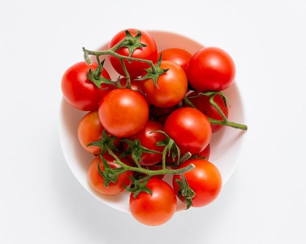 Помидоры черри в миске на белой предпосылке. вид сверху свежих овощей.
