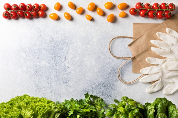 Cherry tomatoes and lettuce near gloves and paper bags