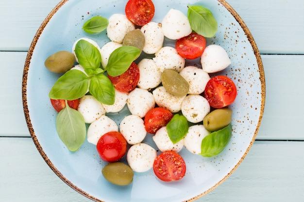Помидоры черри, сыр моцарелла, базилик и специи на доске из серого шифера. ингредиенты итальянского традиционного салата капрезе. средиземноморская кухня.