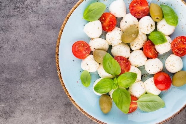 チェリートマト、モッツァレラチーズ、バジル、スパイス、灰色のスレートの石の黒板。イタリアの伝統的なカプレーゼサラダの材料。地中海料理。