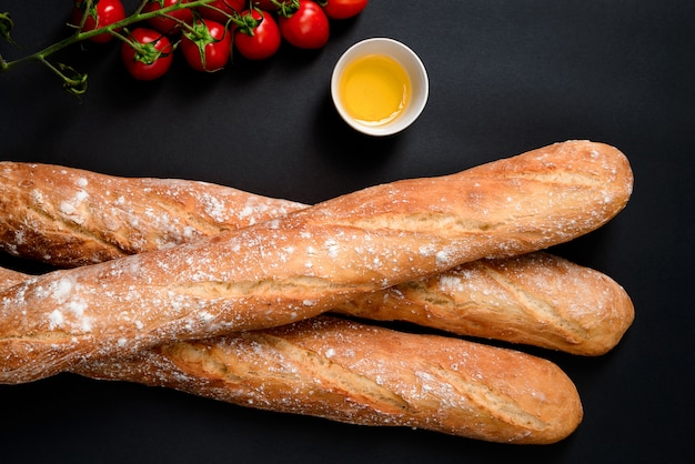Cherry tomatoes, oil and long loafes with flour