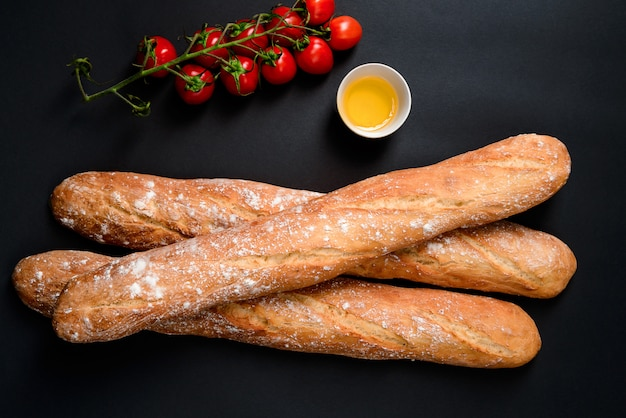 Cherry tomatoes, oil and long loafes with flour.