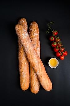 Pomodorini, olio e pagnotte lunghe con farina.