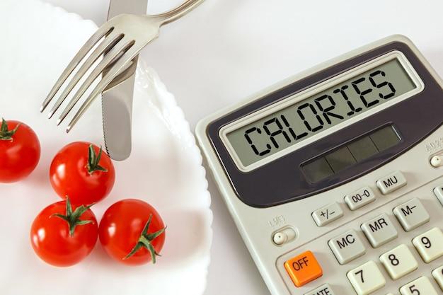 칼 붙이 및 칼로리 계산기와 함께 접시에 체리 토마토