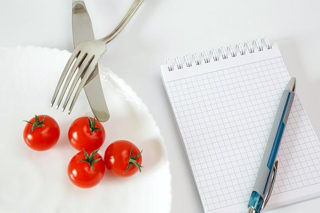 Помидоры черри на тарелке со столовыми приборами тетрадь для записи и подсчета калорий диетического питания