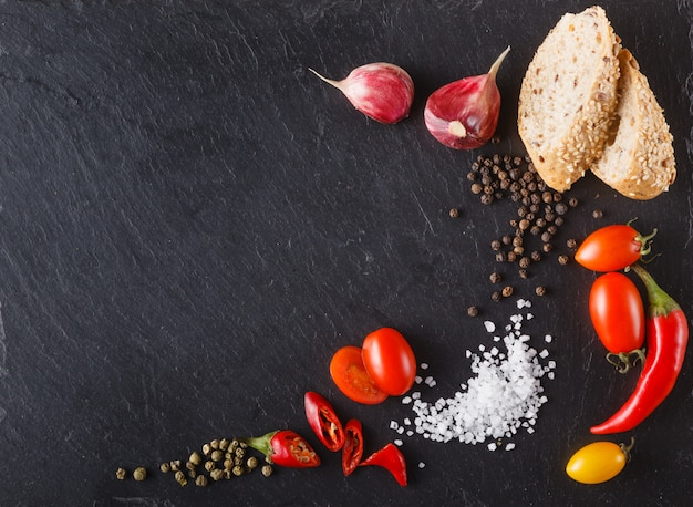 Помидоры черри на сланце с нарезанным хлебом, черным перцем и солью. место для надписи