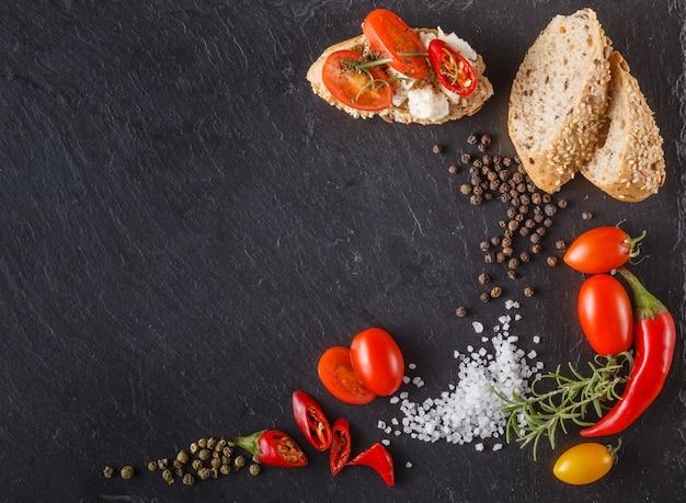Помидоры черри на шифер с ломтиками хлеба, брускетта и соль.