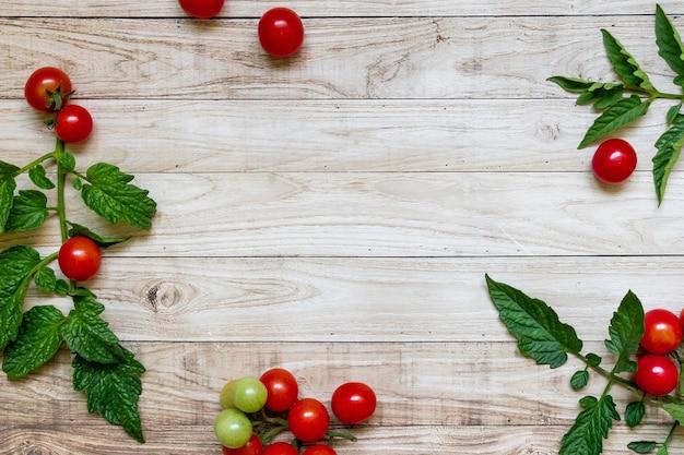 木製のテーブルの背景の暗い光の葉の上のチェリートマト